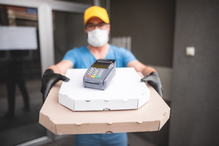 A person in a mask and gloves presenting a couple of boxes with a credit card scanner on top.