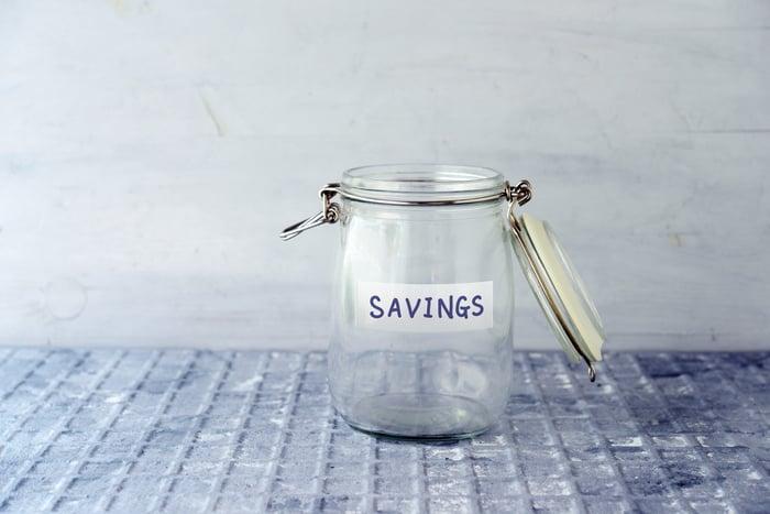 Empty glass jar labeled savings.