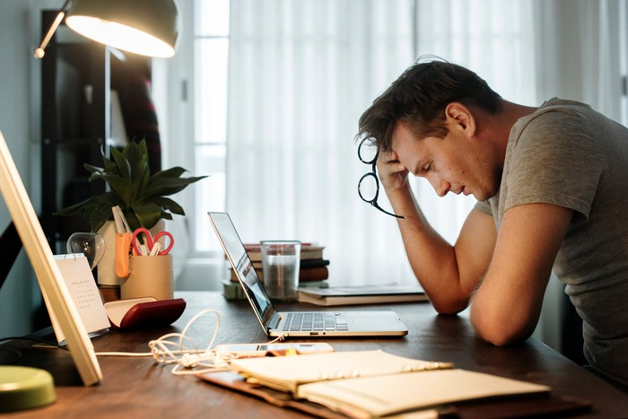 Man at desk in front of laptop, holding his head