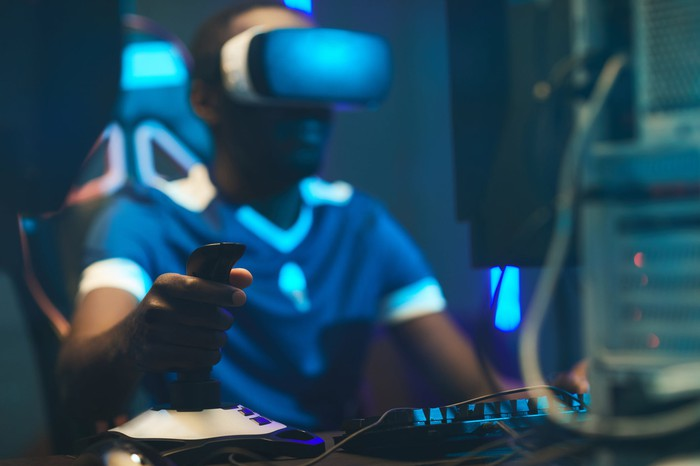 Young man playing a video game using a joystick and VR goggles.
