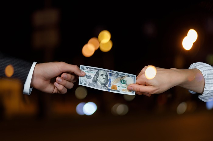 Two hands both trying to take a hundred dollar bill.