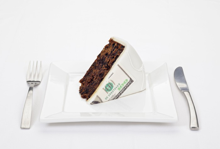 Huge slice of cake served on a plate with a hundred dollar bill printed on the frosting.