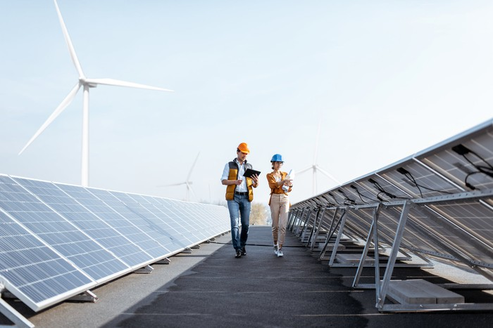 Two people walking by a solar installation with a wind turbine in the background