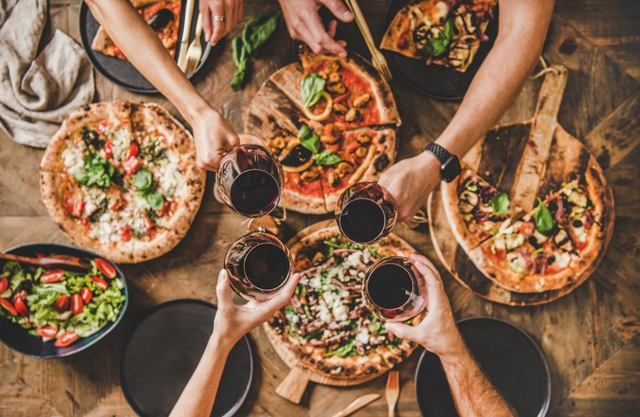 Four people enjoying pizzas and drinks