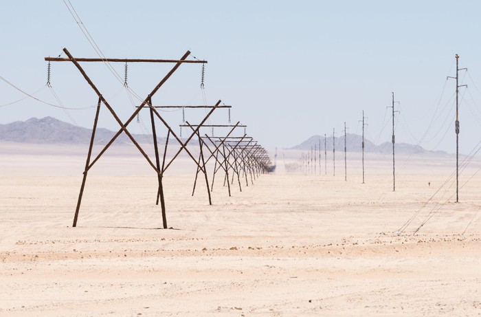 power transmission lines in a desert with background mountains