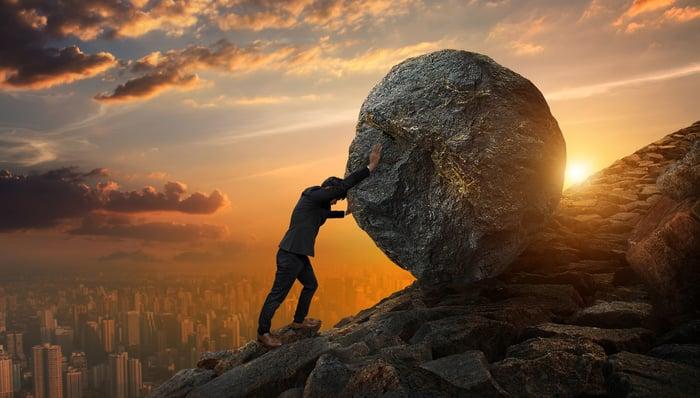 A businessman pushes a boulder uphill.