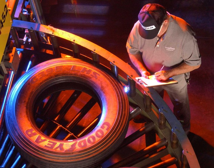 Worker wearing hat next to a conveyor belt with a Goodyear brand tire.