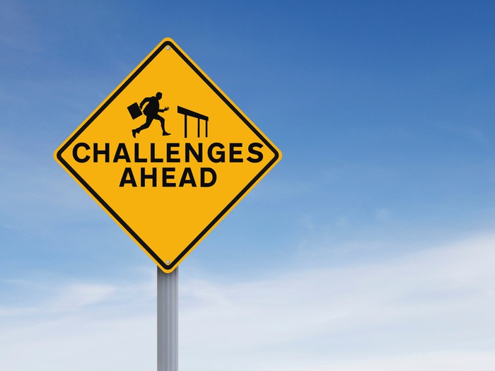 A road sign shows a business person approaching a hurdle and has the words challenges ahead.