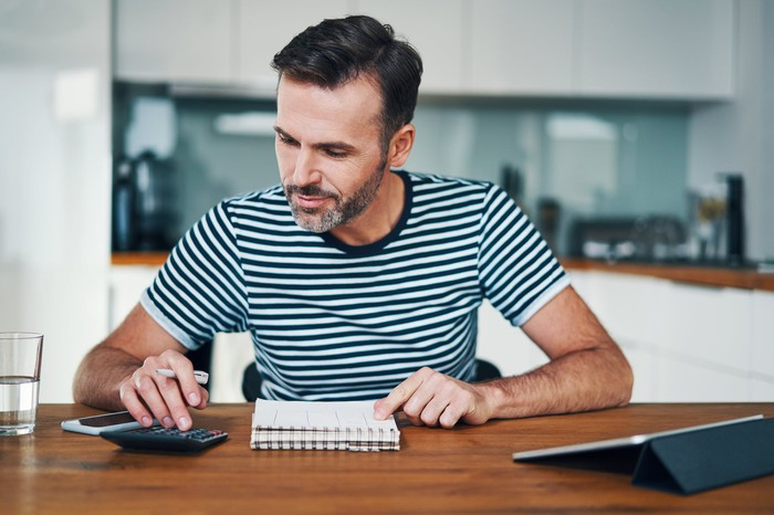 Man at table with one hand typing on a calculator and other pointing to a steno pad.