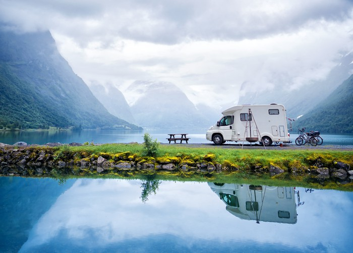 An RV parked at a lake in a scenic location.