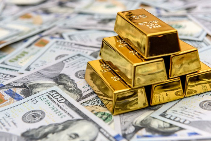A pyramid of gold bars on top of hundred-dollar bills.