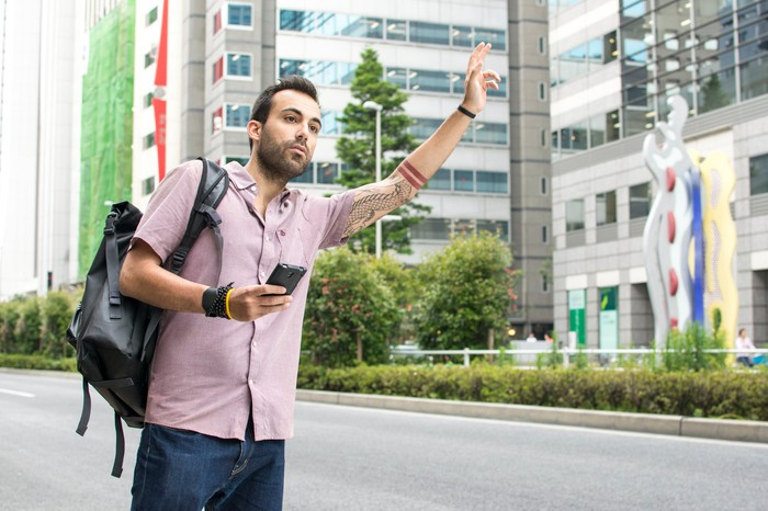 Young man holding a cellphone and wearing a backpack hailing a ride on a city street.