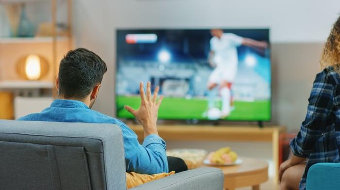 Man watching soccer on big screen tv.