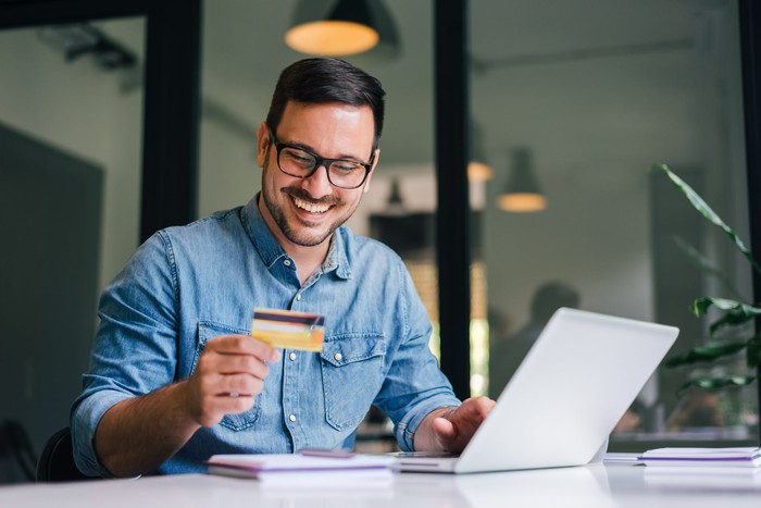 A young man smiles at his credit card while on his laptop.