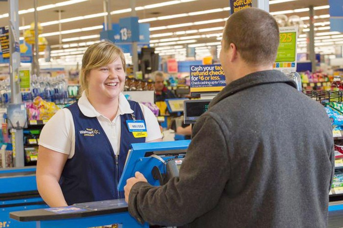 A customer interacting with a smiling Walmart cashier.
