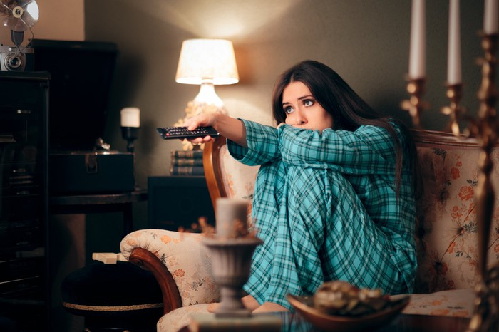 A bored woman wearing pajamas on a couch pointing her TV remote