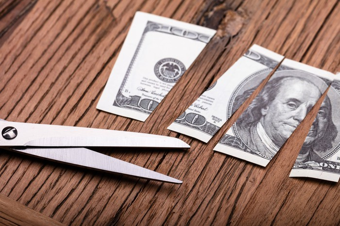 Pair of scissors and a cut up $100 bill