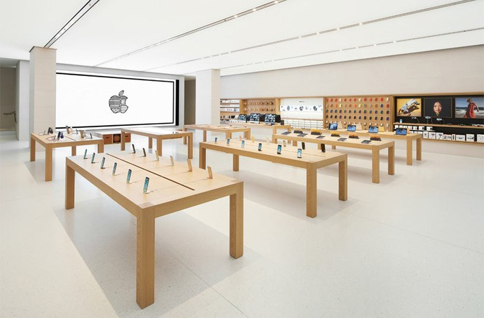 Tables displaying Apple devices at an Apple store.