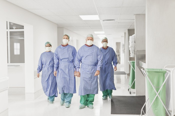 Four doctors with masks walking down hospital corridor.