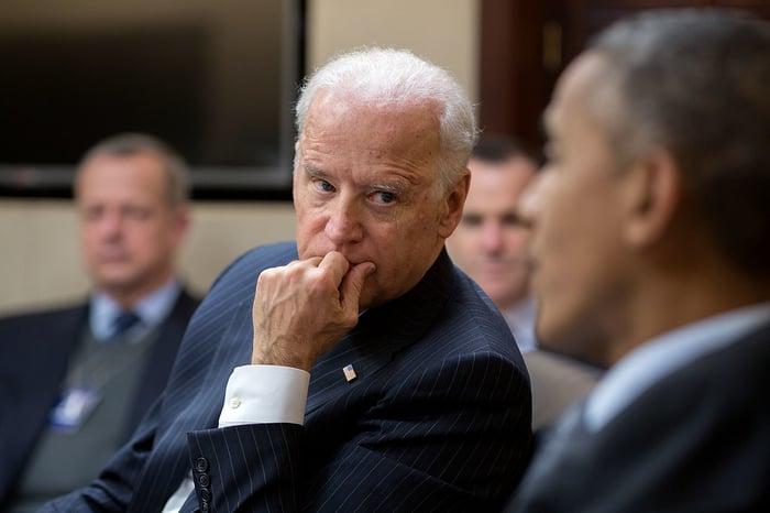 Joe Biden listening to Barack Obama speak during a meeting.