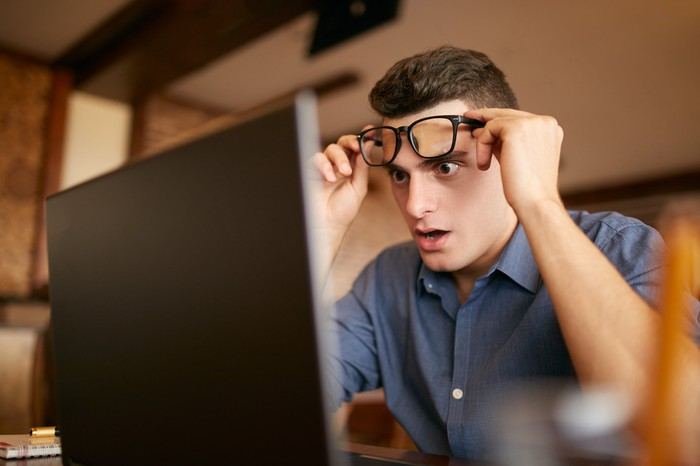 Shocked man looks at laptop screen