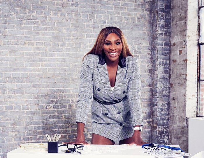 Serena Williams in a business suit behind a desk.