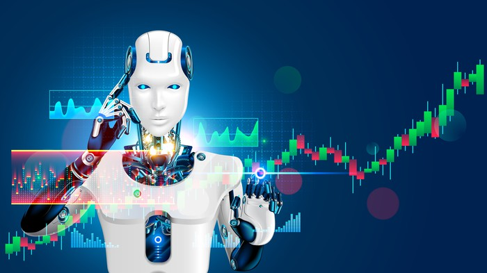 Standing behind a series of stock charts, a robot touches a finger to its head.