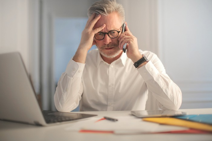 Older man at desk with serious expression holding his head while on phone