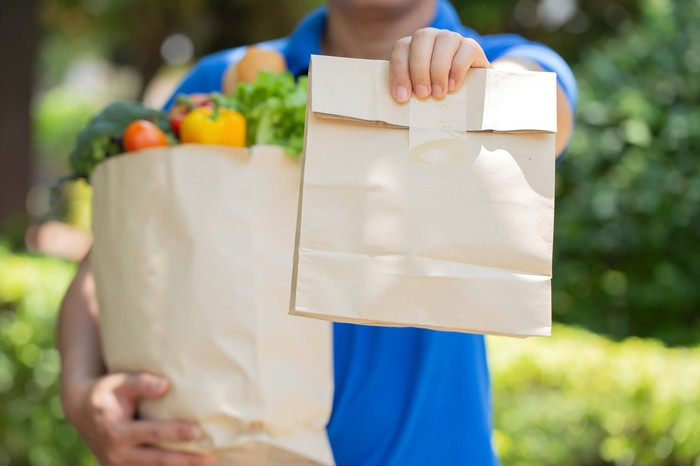 A delivery man seen from the neck down carrying groceries and holding out a sealed paper bag.