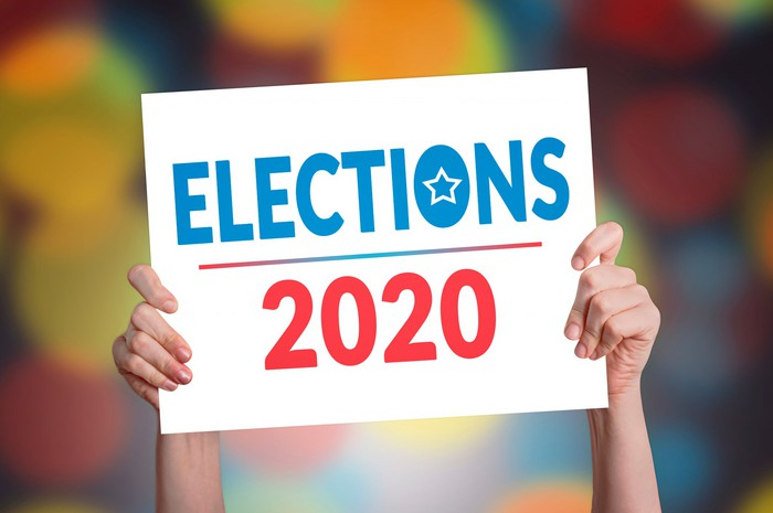 """Hands holding up poster with """"Elections 2020"""" printed on it"""