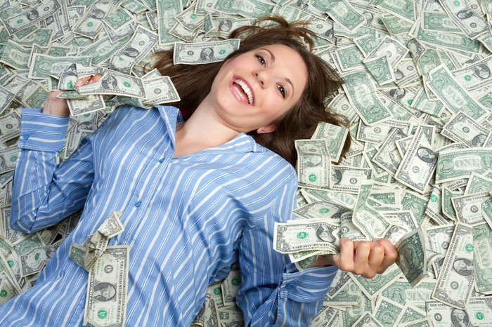 Smiling person lying on top of a pile of one dollar bills.