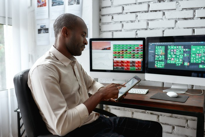 Man holding a smartphone with two computer monitors on his desk