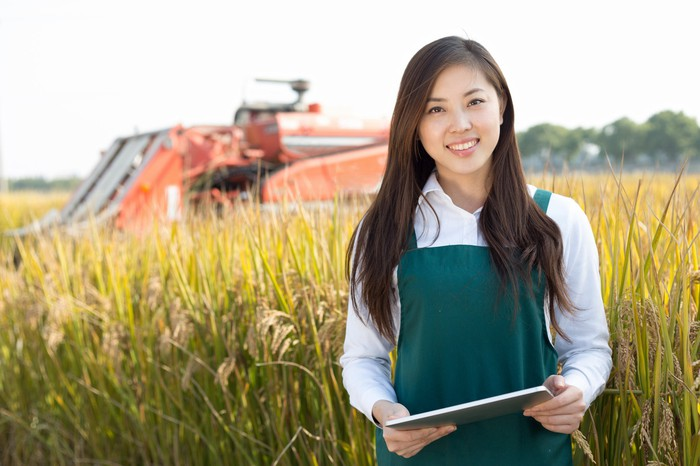 A young woman smiles holding a tablet in a field in front of farm equipment.
