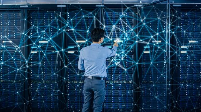 An IT professional checks racks of servers.
