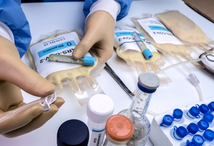 A doctor holding bags of human plasma.