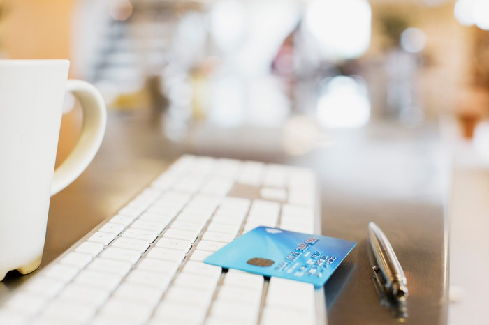 A computer keyboard with a credit card on top of it, next to a pen and cup