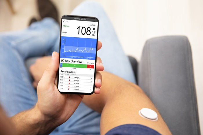 Person holding smart phone displaying blood sugar level