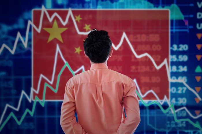 A man examines a stock chart superimposed on a Chinese flag.