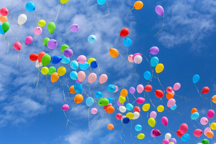 Many balloons against a blue sky