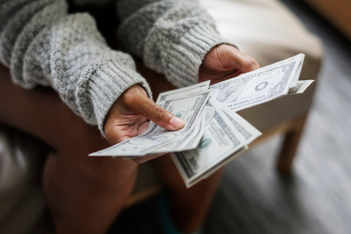 A woman's hands hold a fan-shaped set of banknotes.