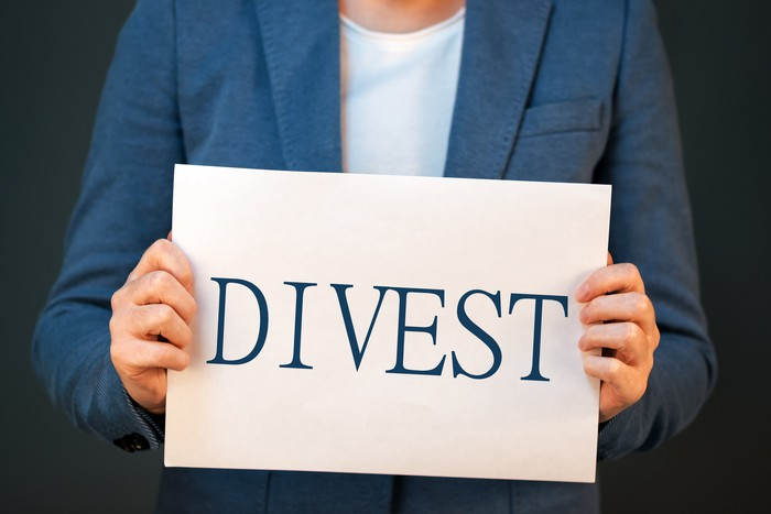 A woman holds a sign that says Divest