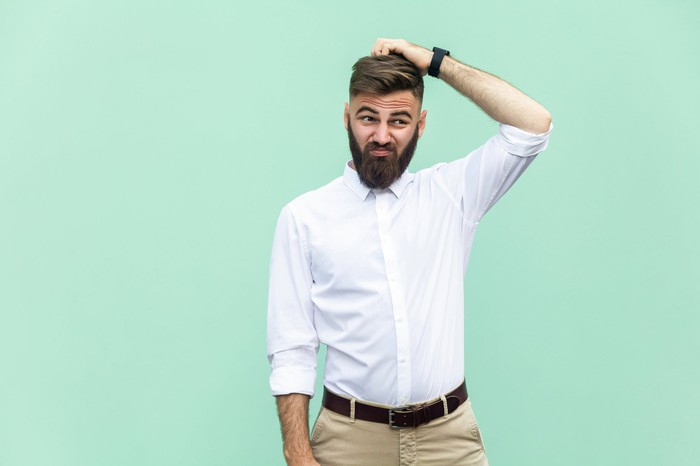Person in a beard, khakis, and a button-up shirt scratching their head with a confused expression on their face.