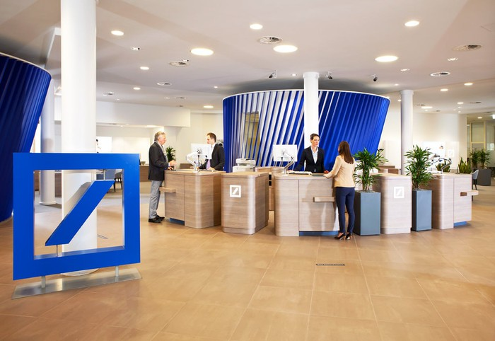 Tellers helping customers at a Deutsche Bank