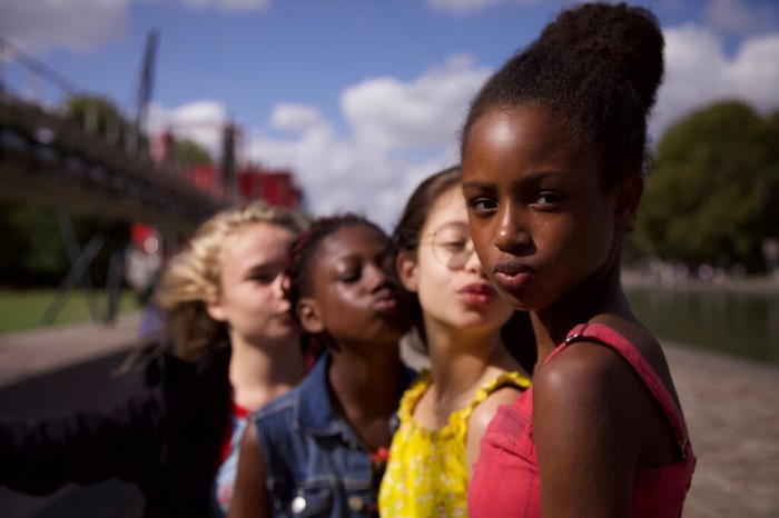 Photo of a group of young girls looking at camera. One of them looks stern.