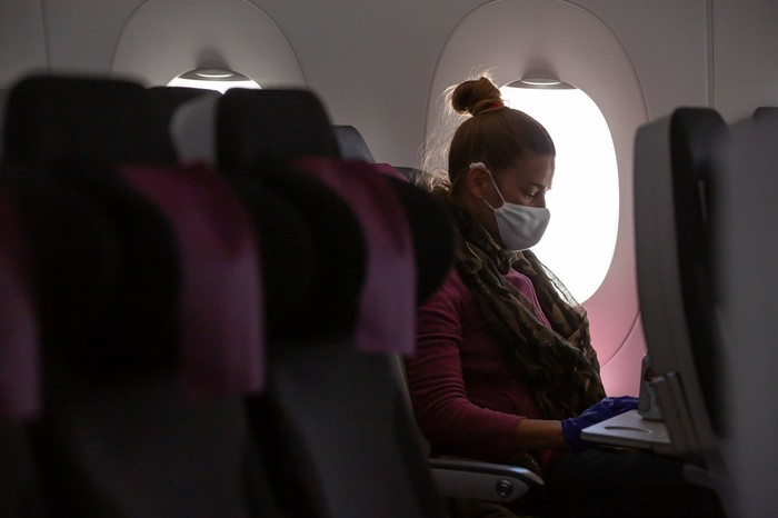 Airline passenger wearing face covering.