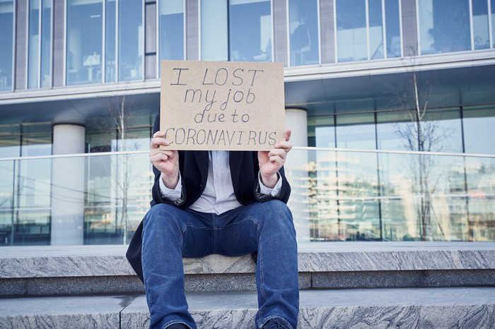 Man sitting in front of office building holding a sign that says he lost his job due to coronavirus.