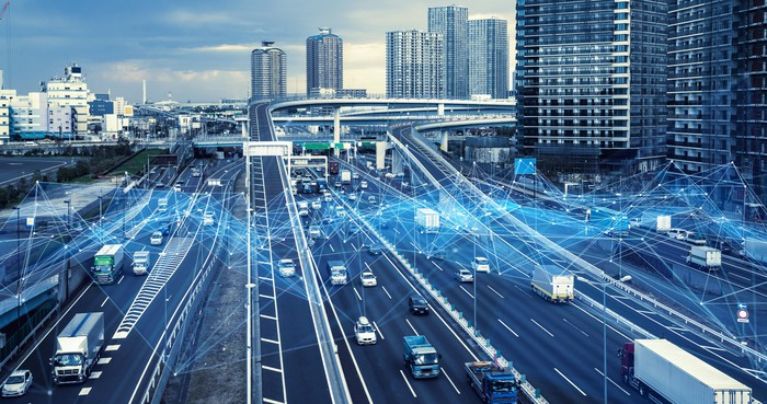 Cars driving on an urban freeway and blue lines signifying wireless linkages.