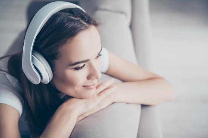 Woman enjoying listening to content on wireless headphones.