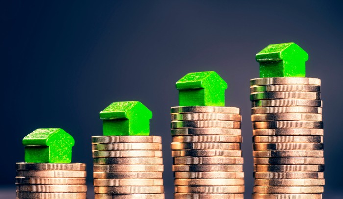 Miniature wooden houses are on top of rising stacks of gold coins.
