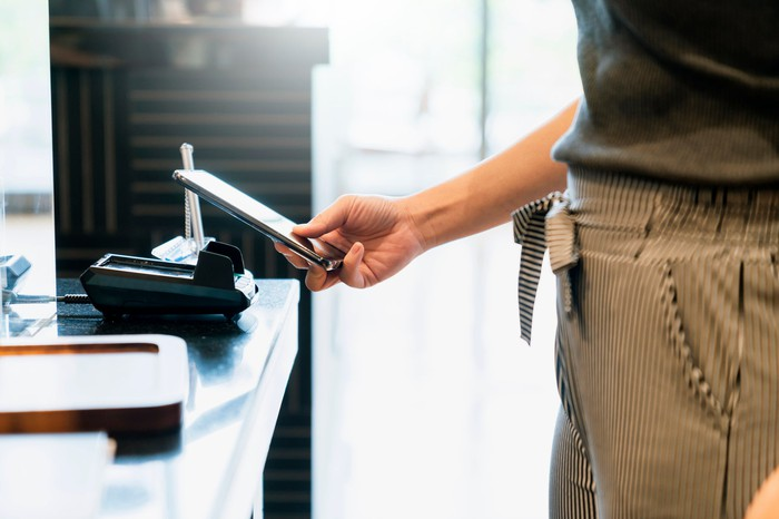 A person holding a smartphone near a touchless digital payment terminal.